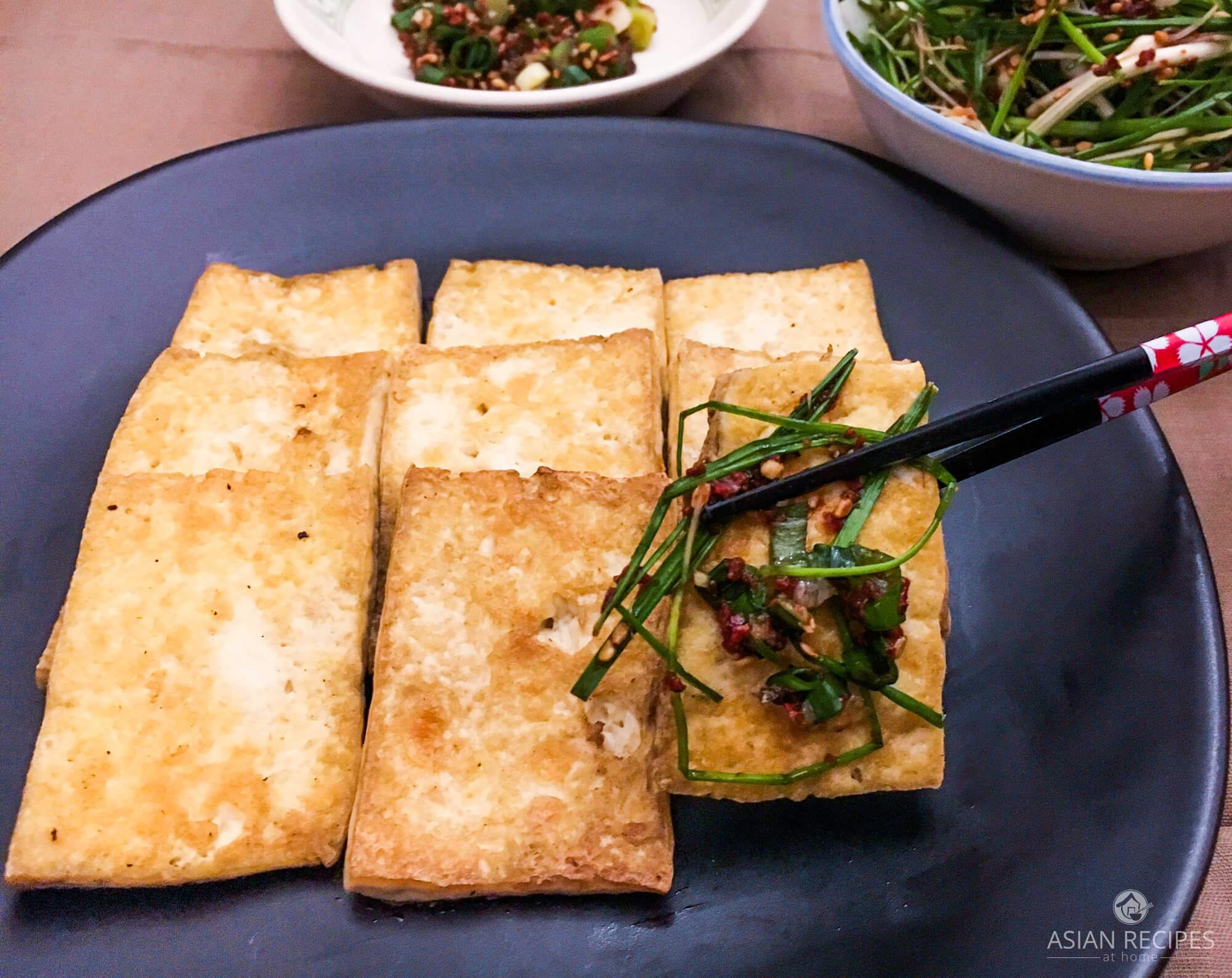Picking up a piece of pan-fried tofu with our chive salad and sauce.