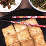 Freshly made pan-fried tofu ready to eat with dipping sauce.