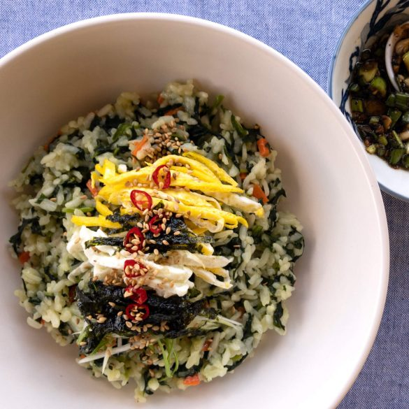 Korean spinach rice is served with pan-fried egg strips, strips of roasted seaweed, and topped with a drizzle of our savory Sesame Green Onion sauce.