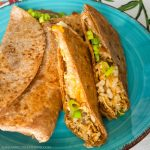 Delicious kimchi fried rice, chicken, cheese, tomatoes, and onions are packaged nicely in a browned tortilla.