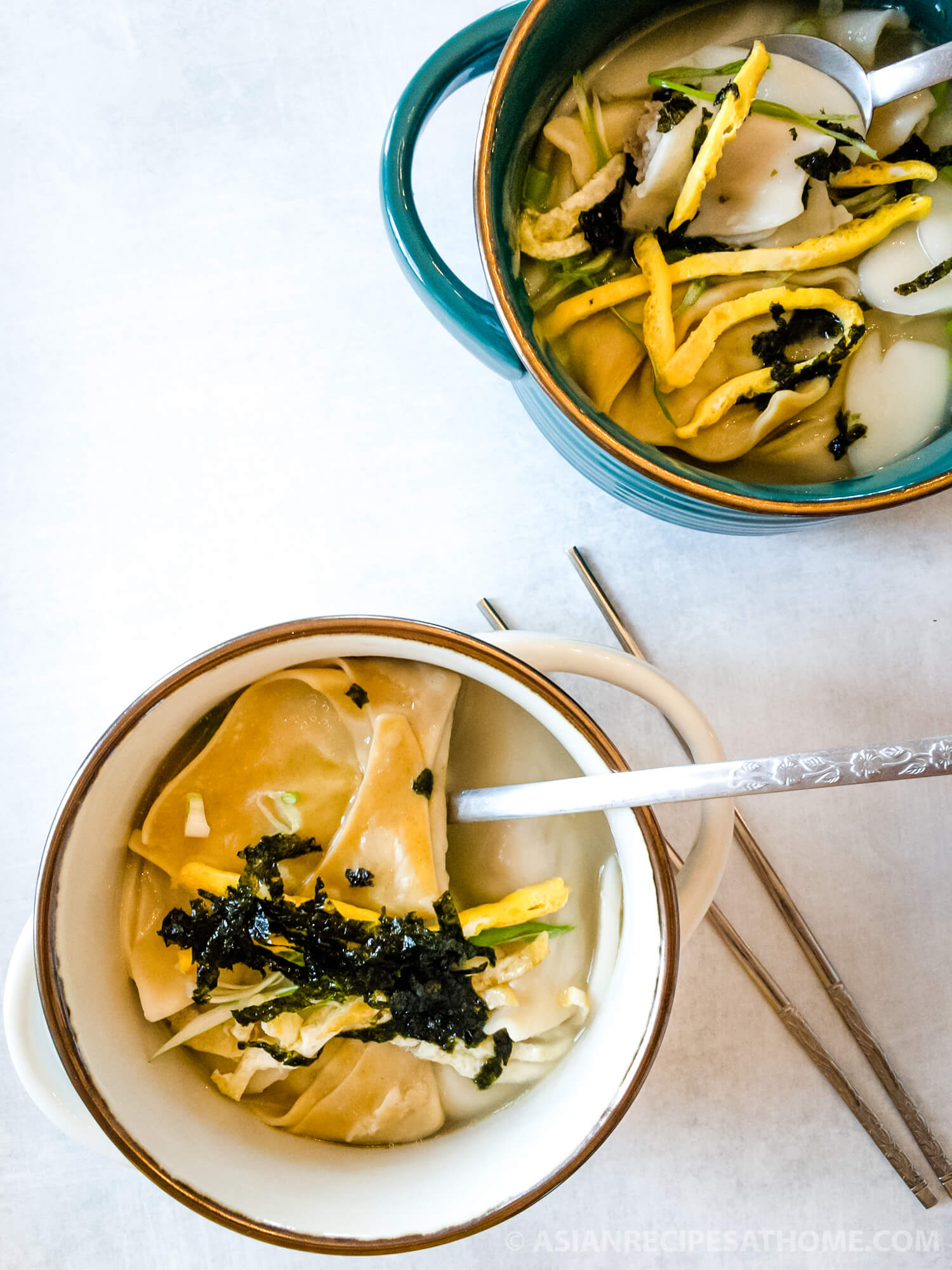 Korean rice cake soup is a savory and delicious soup made of sliced rice cakes and dumplings in a clear broth.