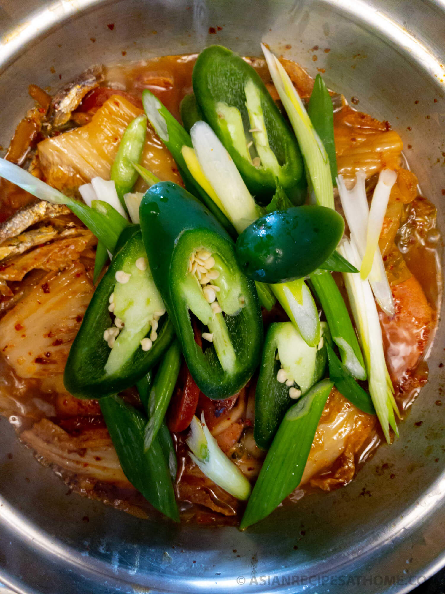 Adding in sliced jalapenos and green onions to our kimchi stew