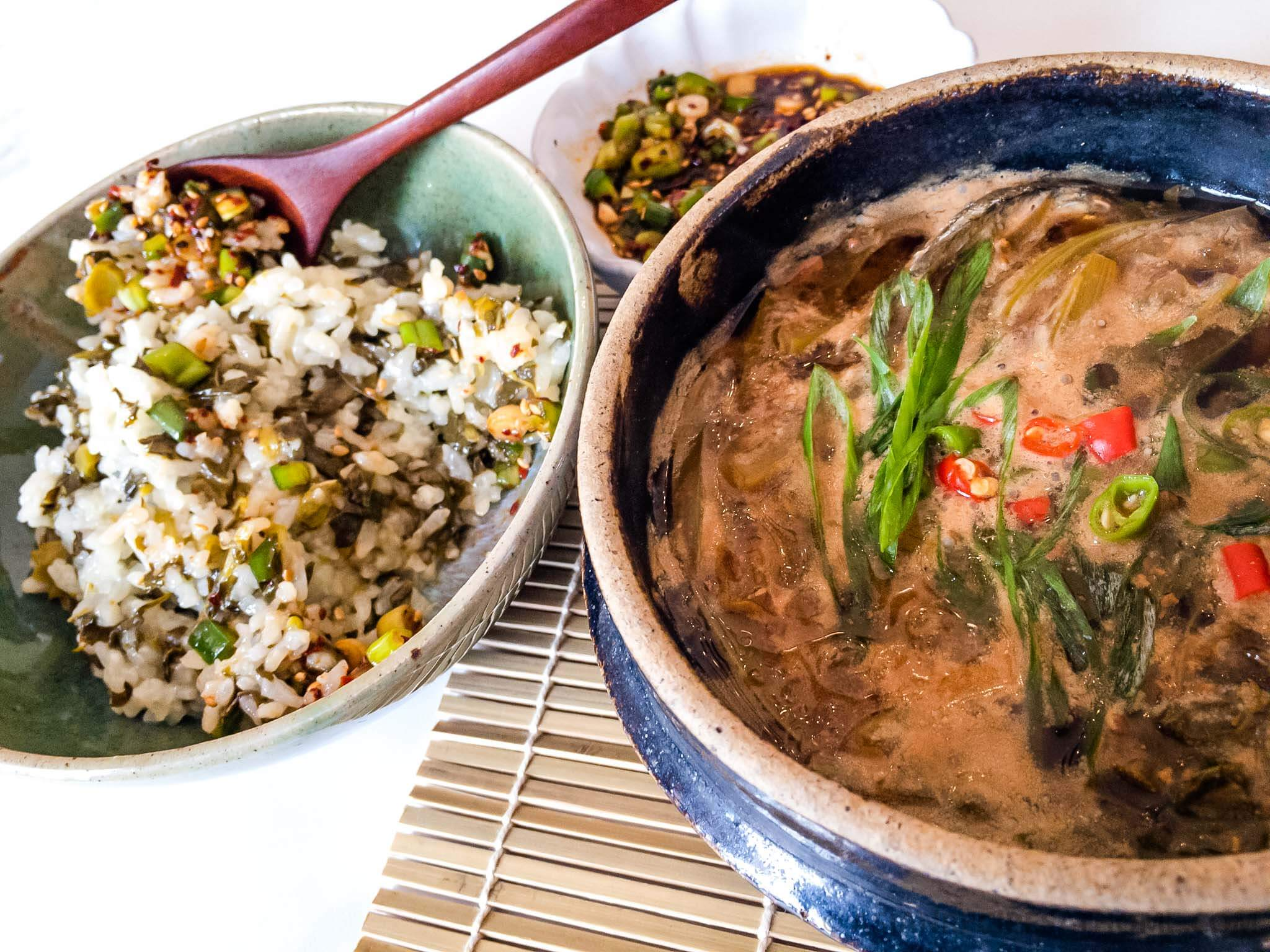 Stone pot filled with Korean Soybean Paste Stew (Doenjang Jjigae) recipe with the addition of delicious poke salad (sallet) and a side of our Asian-style poke salad (sallet) rice.