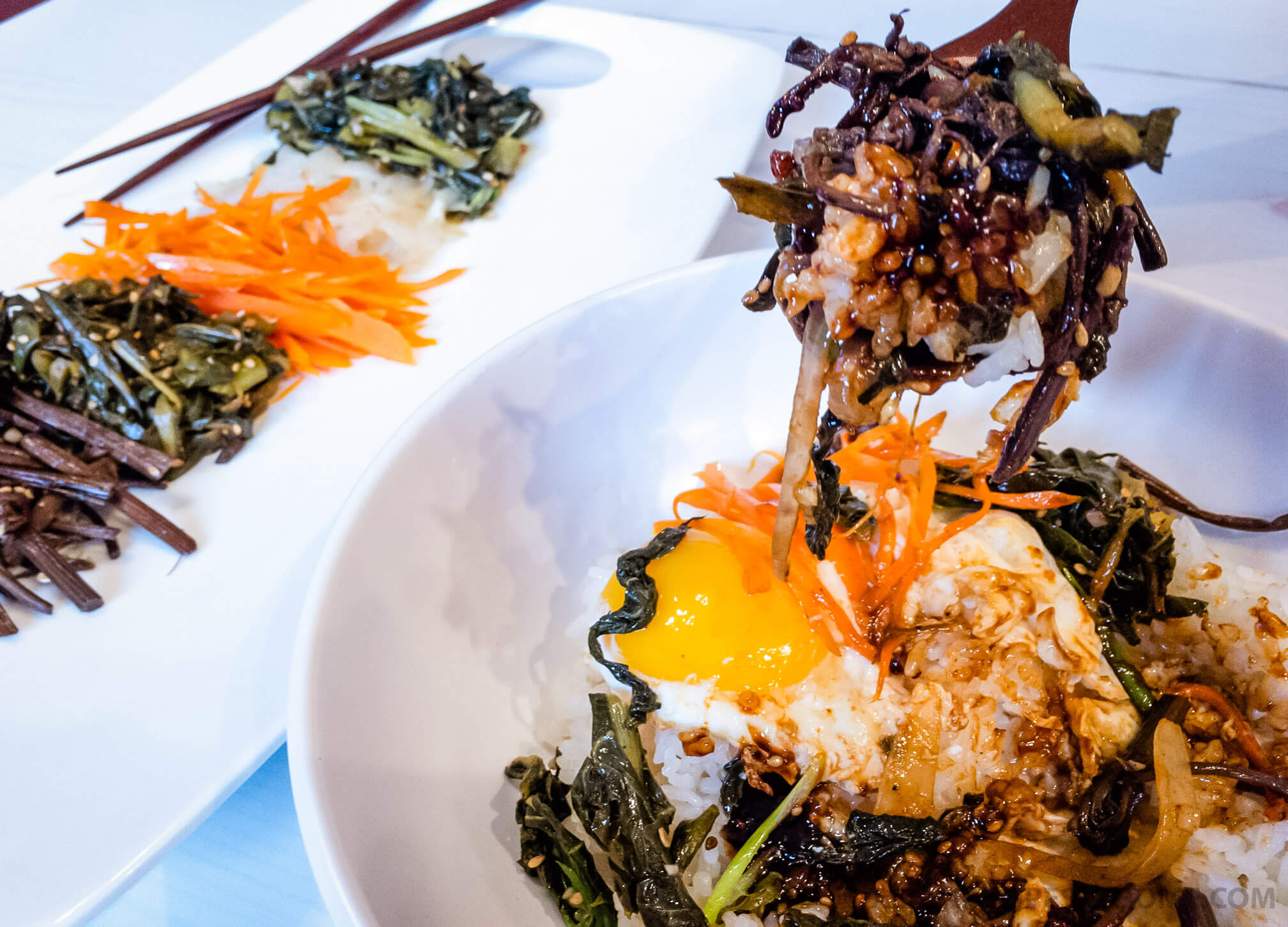 This version of Korean bibimbap is full of a variety of vegetables, including poke salad (sallet), with a fried egg on top and drizzled with a spicy gochujang sauce.