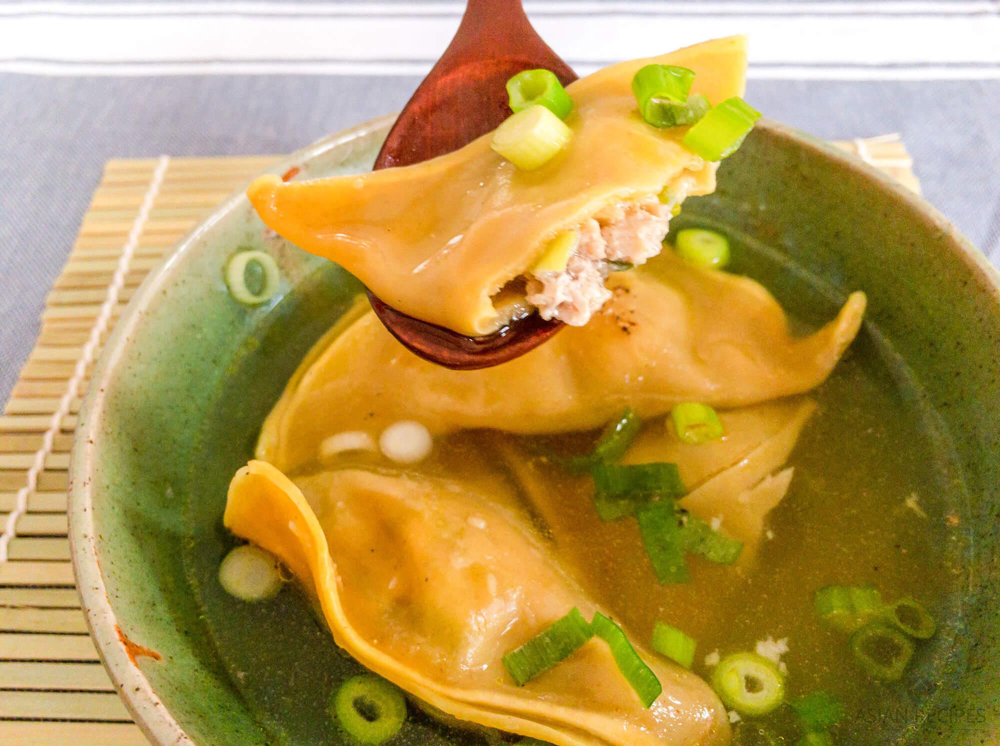 A spoon full of a Korean dumpling (mandu) in a clear broth based soup.