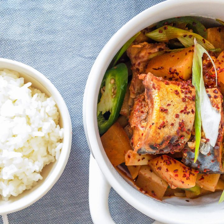 Mackerel fish and Korean radish are the stars in this delicious and spicy Korean braised dish and is shown with a bowl of freshly steamed rice.