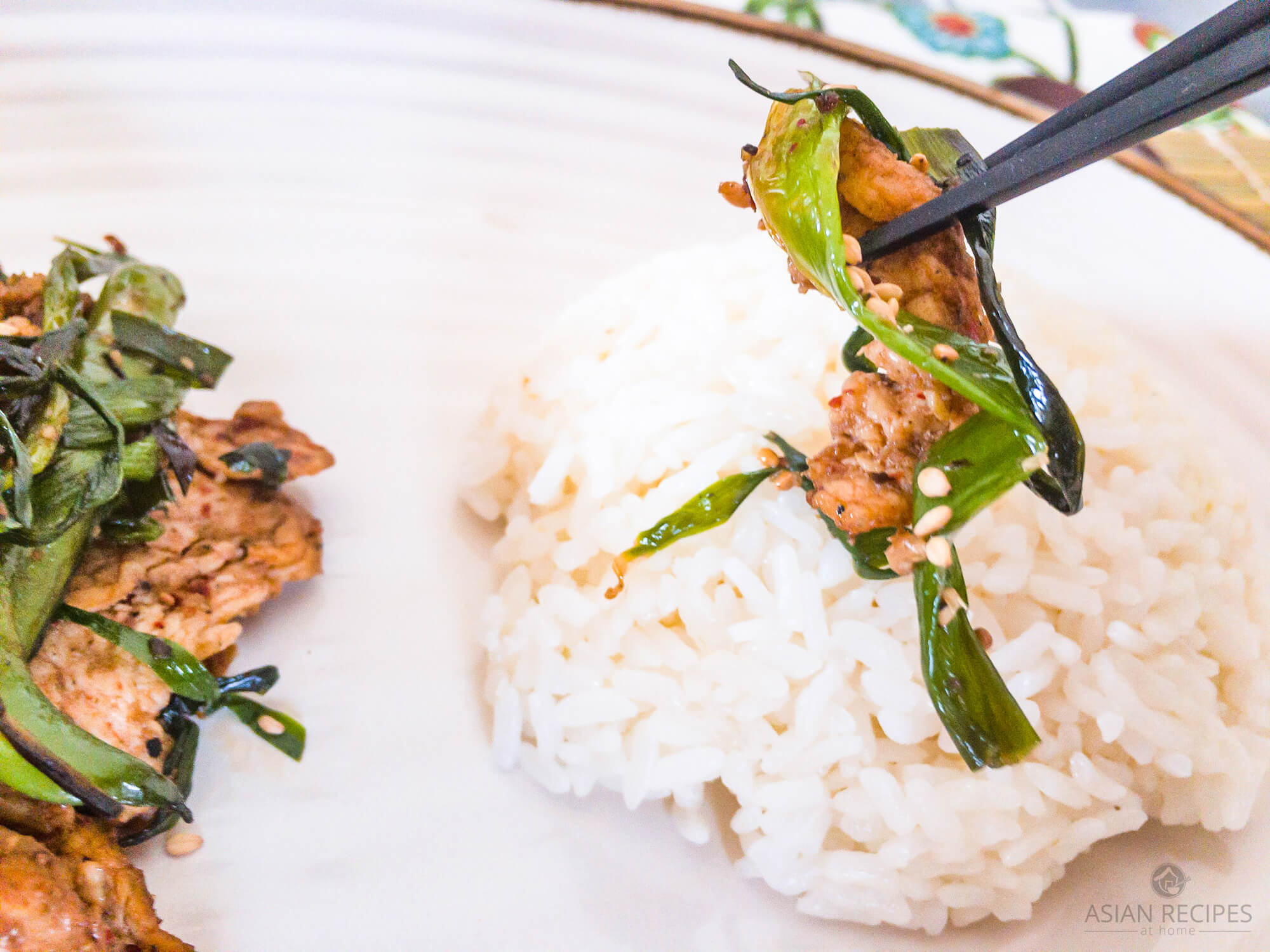 Juicy and thinly sliced chicken thighs are stir-fried in a homemade spicy kimchi sauce pictured on a white plate with steamed rice.