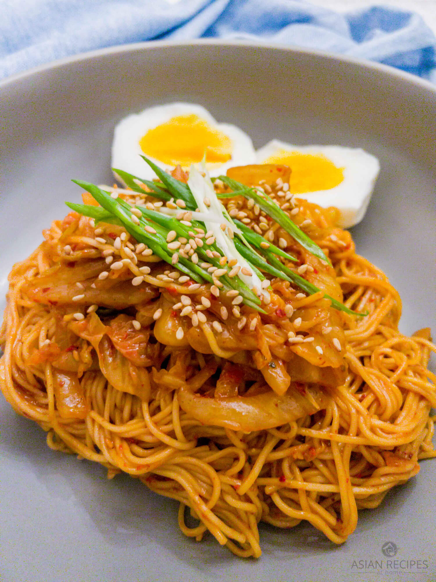 Our spicy cold noodle recipe is covered in a Korean red chili pepper paste (gochujang) sauce with thinly sliced aged kimchi.