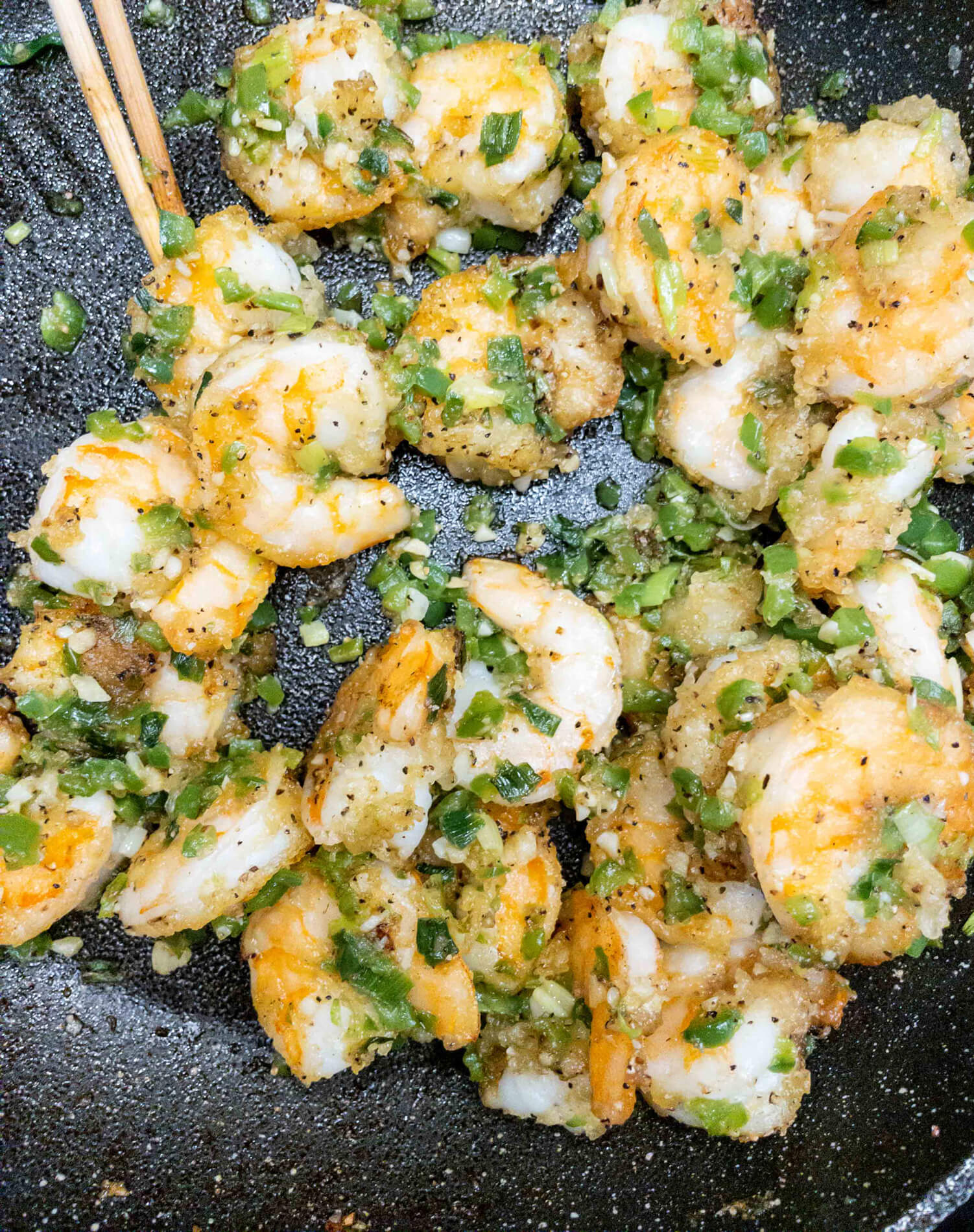 Shrimp are fried in avocado oil to a golden brown and tossed with peppers, garlic, green onion, salt, and pepper.